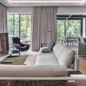 Piękny salon z oknami do sufitu i zasłonami w kolorach ziemi. Projekt BAJERSOKÓŁ team. Fot. Tom Kurek