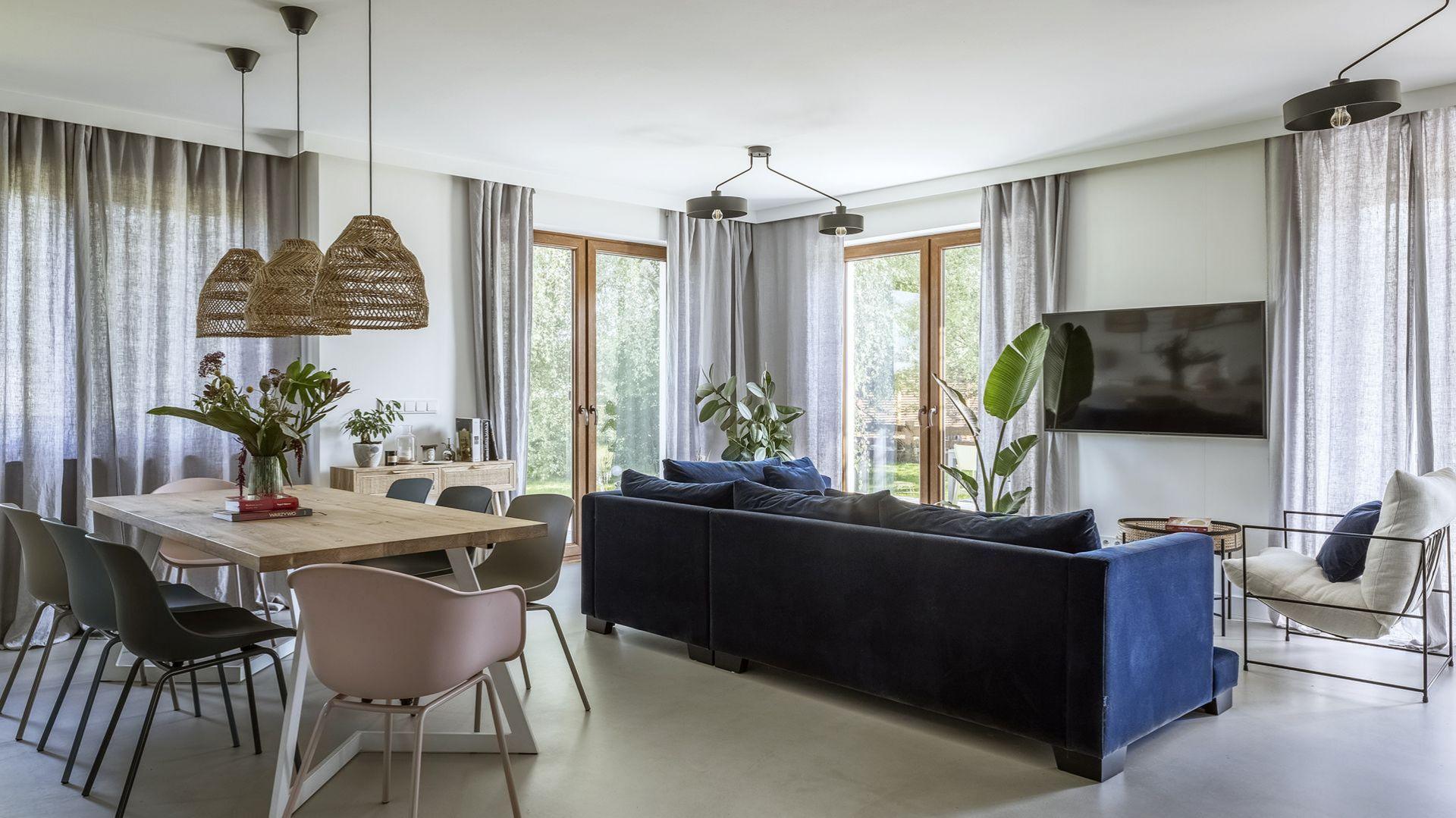 W tym salonie szare przejrzyste zasłony z ukrytym karniszem ocieplają wnętrze i dodają mu elegancji. Projekt Malwina Morelewska. Fot. Yassen Hristov