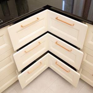 Projektanci postawili na wygodę użytkowania, wykorzystując szuflady narożne, które pozwalają na optymalne wykorzystanie kłopotliwej przestrzeni. Na zdj. Kuchnia na miedziany połysk od ernestrust
