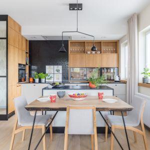 Kuchnia otwarta na salon z jadalnią stanowi znaczące tło dla całej aranżacji. Projekt Agnieszka Morawiec. Fot. Pion Poziom