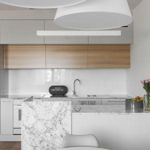 Biel i marmur podkreślą elegancki charakter przestrzeni kuchennej. Projekt MAFgroup