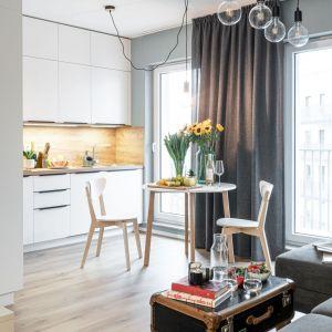 W prostym i ponadczasowym salonie także oświetlenie jest minimalistyczne - to modne żarówki  w loftowym stylu. Projekt i zdjęcia pracownia KODO Projekty i Realizacje Wnętrz.jpg