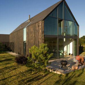 """Pomysł na surową, """"naturalną"""" formę budynku przejawia się w wykończeniu elewacji pokrytej deskami z modrzewia. Projekt: Ola Wołczyk. Fot. Hanna Długosz"""