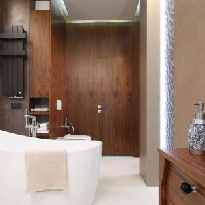 Salon kąpielowy zaaranżowany z wanną wolnostojącą i w drewnie wygląda elegancko i luksusowo. Projekt Laura Sulzik. Fot. Bartosz Jarosz