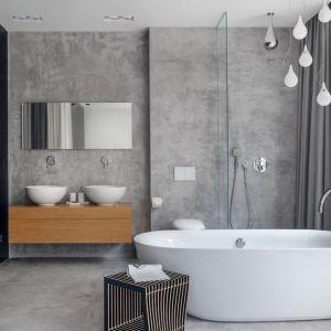 Piękny salon kąpielowy przy sypialni  - szare płytki ścienne i podłogowe, biała wanna wolnostojąca i stylowa armatura łazienkowa. Projekt Studio Maka. Fot. Tom Kurek.jpg