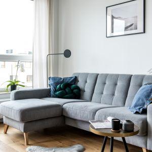 Szara sofa z charakterystycznym pikowaniem nadaje niedużemu salonowi stylowy wygląd. Projekt Deer Design