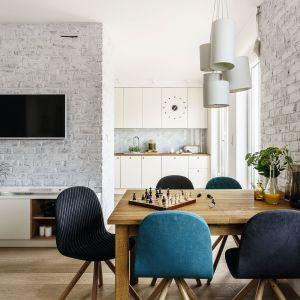 Salon z jadalnią, ulokowaną zazwyczaj w pobliżu otwartej kuchni, sprawdzi się zarówno w obszernych, jak i niedużych mieszkaniach. Projekt Saje Architekci. Fot. Fotomohito
