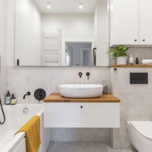 Jasną łazienkę ocieplają drewniane elementy, powiększa zaś duże lustro. Projekt i zdjęcia: Renata Blaźniak-Kuczyńska, Renee's Interior Design