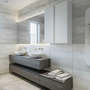 W łazience dominują szarości i biele przełamane ciemnymi detalami. Projekt i zdjęcia: Naboo Studio
