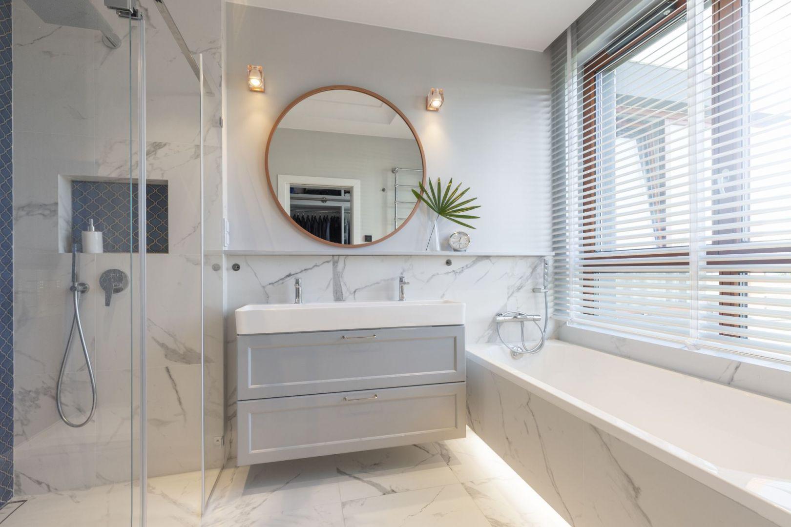 W jasnej łazience głównym motywem aranżacyjnym są płytki imitujące marmur. Ciemniejszą kolorystykę zastosowano w strefie prysznica. Projekt: Decoroom. Fot. Pion Poziom