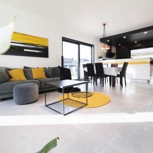 Bardzo nowoczesny salon w czerni i bieli dzięki żółtym poduszkom stał się pełen energii i jaśniejszy. Projekt: Joanna Ochota. Fot. Maciej Sułek