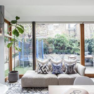Kolorowe wzorzyste poduszki dekorują szarą kanapę w nowoczesnym salonie. Projekt: Tamara Tymowski, Sybaris Design. Fot. Zajc
