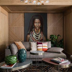 W tym modnym nowoczesnym salonie w kolorach ziemi beżową kanapę dekorują piękne poduszki w ciepłych barwach. Projekt: Magdalena Bielicka, Maria Zrzelska-Pawlak. Fot. Fotomohito