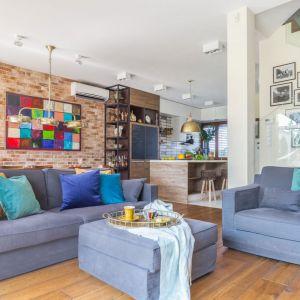 Do szarej kanapy dobrano poduszki w kolorach niebieskich i żółtych. Projekt: Monika Pniewska. Fot. Pion Poziom