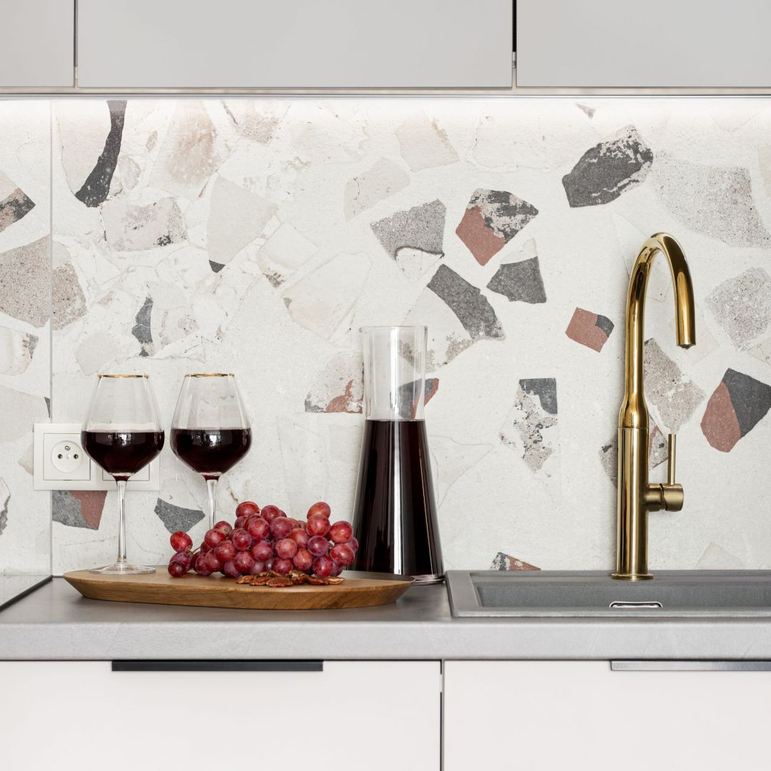 Mosiężne dodatki takie jak bateria kuchenna czy lampa sufitowa budują elegancką aranżację wnętrza. Projekt: Maria Nielubszyc, pracownia PURA design. Zdjęcia: Jakub Nanowski