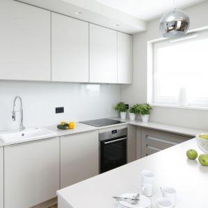 Szkło nad blatem w kuchni tworzy spójną całość z białą zabudową kuchenną. Projekt: Katarzyna Uszok. Fot. Bartosz Jarosz