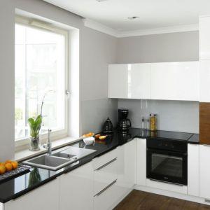 Ścianę nad blatem zdobi szare szkło, które doskonale pasuje do bieli i drewna. Projekt: Karolina Łuczyńska. Fot. Bartosz Jarosz