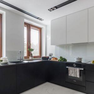 Białe szkło nad kuchennym blatem doskonale sprawdziło się w minimalistycznej, czarno-białej kuchni. Projekt: Decoroom. Fot. Marta Behling, Pion Poziom Fotografia Wnętrz
