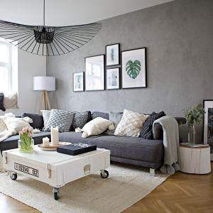 Szara ściana z efektem betonu, szara kanapa, stolik na kółkach, lampa-kapelusz. Projekt: SHOKO design