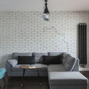 Białą cegłą wykończono całą jedną ścianę w salonie. Jasna kolorystyka optycznie powiększa niedużą, otwartą strefę dzienną. Projekt: Anna Nowak-Paziewska. Fot. Emi Karpowicz