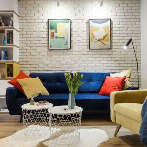 Na tle białej cegły świetnie wygląda niebieska kanapa z kolorowymi poduchami. Projekt i zdjęcia: KODO Projekty i Realizacje