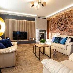 Cegła zdobiącą ścianę za kanapą doskonale pasuje do ciepłej brązowo, beżowej kolorystyki zastosowanej w salonie. Projekt: Anna Kamińska, Fuxja Studio Projektowe. Fot. Alla Boroń