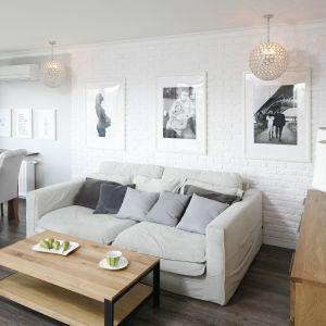 Ścianę za kanapą zdobi biała cegła na tle, której ładnie wyeksponowano rodzinne zdjęcia. Projekt: Marta Kramkowska. Fot. Bartosz Jarosz