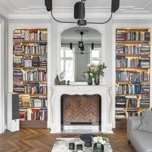 W tym salonie dość pokaźna biblioteczkę zaplanowano po dwóch stronach kominka. Projekt: Whitecastle.pl. Fot. Tom Kurek