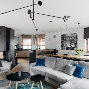 Dwa czarne, nieduże stoliki idealnie pasują do szarej kanapy i czarnych elementów wysposażenia w salonie. Projekt: Estera Sosnowska, Robert Sosnowski. Fot. Foto&Mohito