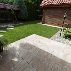 Wyniesienie tarasu ponad poziom działki to często stosowany zabieg, który wizualnie podkreśla jego rolę jako przedłużenia salonu na ogród. Fot. Polbruk