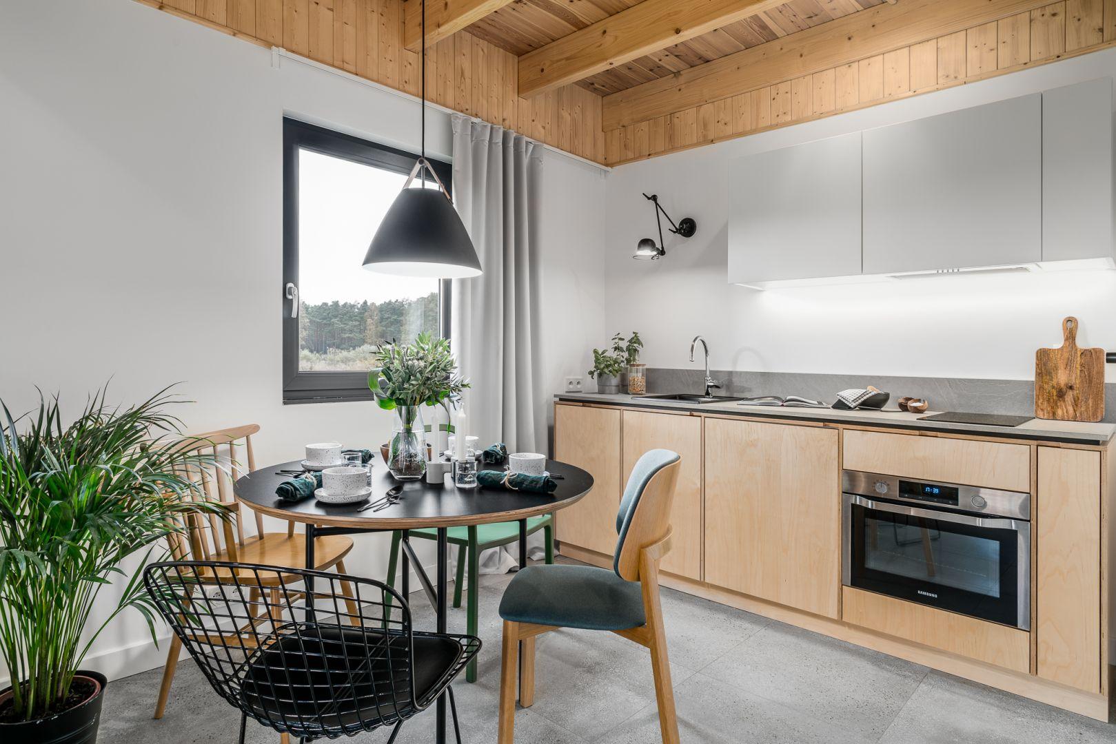 Kompaktowa kuchnia zawiera wszystkie dogodności, takie jak zmywarka czy piekarnik z mikrofalą. Projekt: Raca Architekci. Fot. Fotomohito