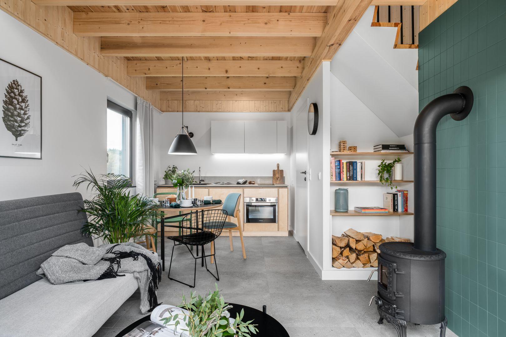 Parter domku stanowi salon z aneksem kuchennym i przestronna łazienka. Projekt: Raca Architekci. Fot. Fotomohito