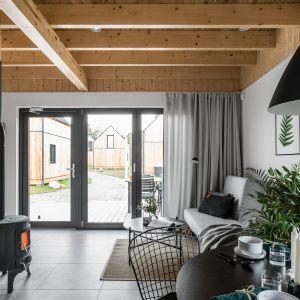 Z domku jest wyjście na drewniany taras. Projekt: Raca Architekci. Fot. Fotomohito