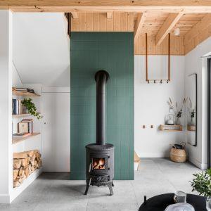 Głównym elementem salonu jest mały kominek stojący na tle ściany kominowej wykończonej małymi płytkami w kolorze naturalnej zieleni. Projekt: Raca Architekci. Fot. Fotomohito