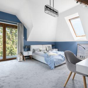 Białe meble z drewnianymi elementami, prosty układ pomieszczenia, duże łóżko, dywan na podłodze, zasłony w oknach... Projekt MM Architekci. Fot. Jeremiasz Nowak