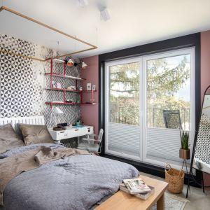 Ścianę za łóżkiem zdobi tapeta z geometrycznym wzorem. Projekt Mikołajska Studio