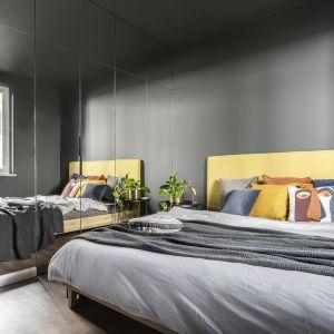 Ścianę za łóżkiem pomalowano na ciemny kolor. Projekt Decoroom. Fot Pion Poziom