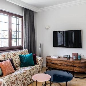 Wyjątkowym elementem w salonie jest zaprojektowana przez architektki szafka RTV. Jej obłe kształty pięknie prezentują teakowy fornir. Projekt: Magdalena Bielicka, Maria Zrzelska-Pawlak, Pracownia Magma. Fot. Fotomohito