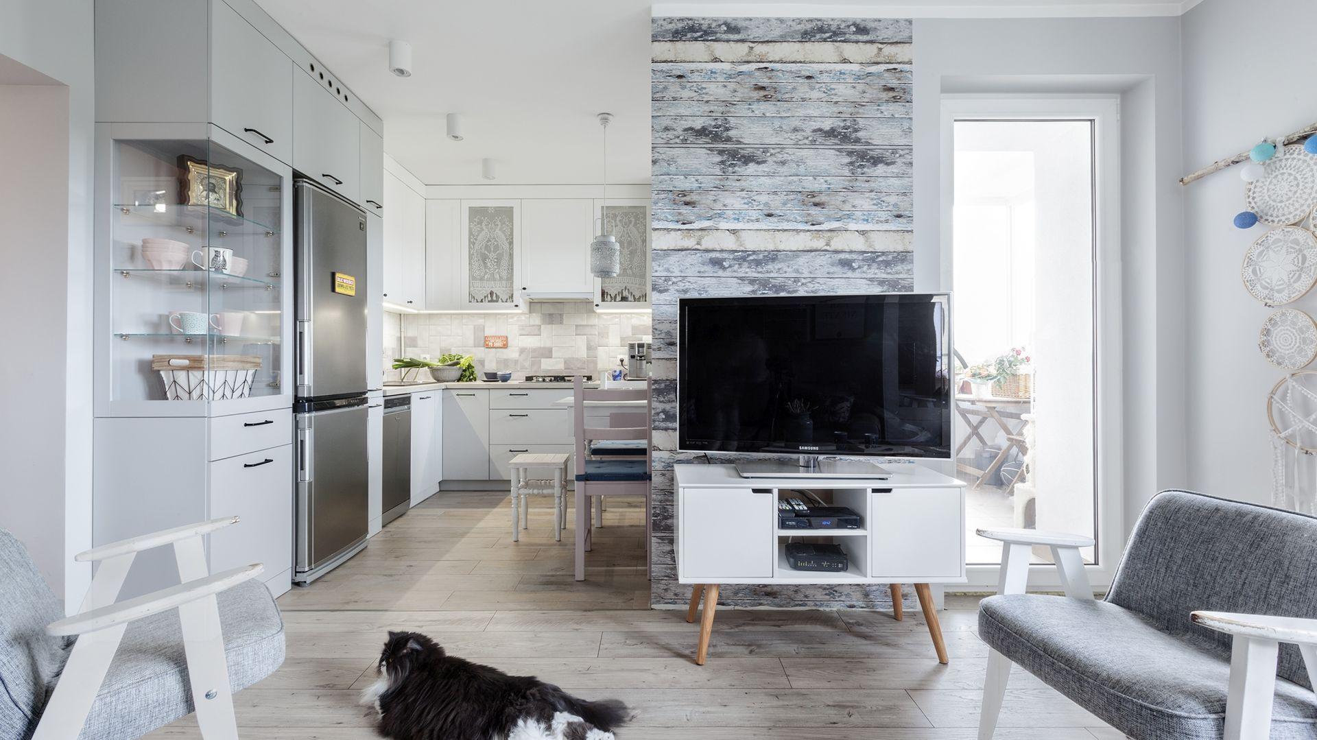 Biała szafka na drewnianych nogach świetnie pasuje do nowoczesnego salonu. Zapewnia miejsce na przechowywanie oraz na ustawienie zdjęcia czy rodzinnych pamiątek. Projekt Justyna Mojżyk. Fot. Monika Filipiuk-Obałek