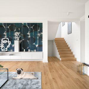 Piękny naturalny salon, z drewnianą podłogą i bardzo ciekawie zaprojektowaną ścianą. Projekt MM Architekci. Fot. Jeremiasz Nowak