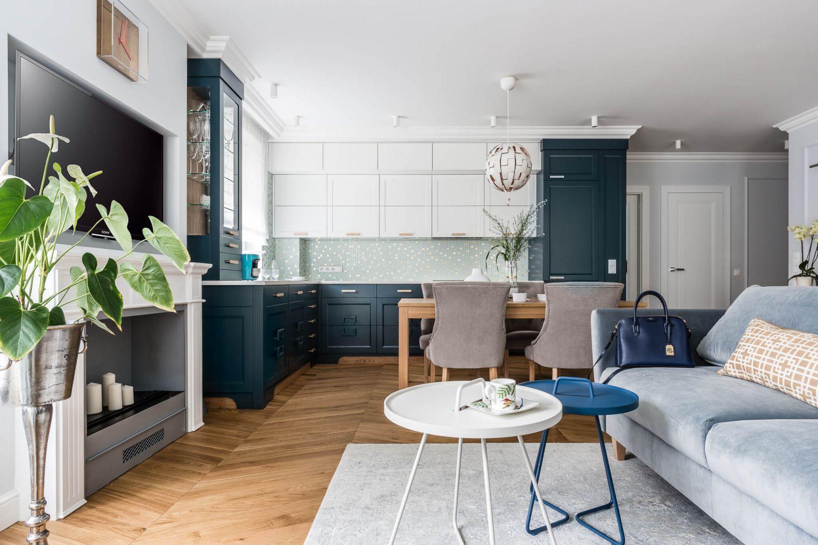 Do jasnoszarej kanapy dobrano dwa okrągłe stoliki w skandynawskim stylu - jeden biały, drugi w modnym granacie. Projekt: Magdalena Bielicka, Maria Zrzelska-Pawlak. Fot. Fotomohito