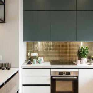 Całość dopełnia złota mozaika, odbijająca blask światła. Industrialny styl podkreśla z kolei czarna oprawa drzwi oraz mebli.