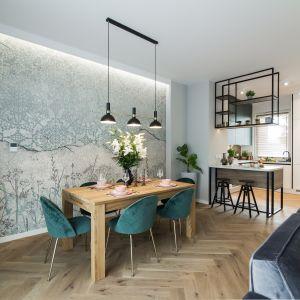 Uwagę przyciąga strefa stołowa – z unikalną tapetą z motywem orientalnym w towarzystwie florystycznych wzorów, a także krzesła z pikowaną tapicerką.