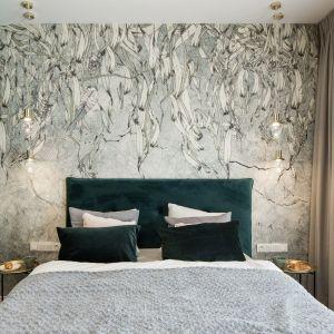 Wzrok przyciąga oryginalna tapeta z naturalnym motywem, prowadząca dialog z zielenią ścian i dyskretnym oświetleniem w stylu vintage.