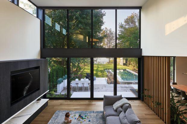 Przeszklona ściana, minimalistyczne wnętrza, nowoczesne meble i spektakularny widok na jezioro - ten dom może się podobać! To projekt dla rodziny z dziećmi!