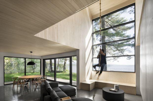 Drewniany dom stoi nad brzegiem malowniczego jeziora. Architektom zależało, aby był weekendową enklawą pozwalającą odpocząć od miejskiego życia. Jak im się udało zrealizować ten plan?