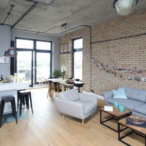 Do nowoczesnego salonu doskonale pasują proste w formie drewniane stoliki. Projekt: Maciejka Peszyńska-Drews. Fot. Bartosz Jarosz