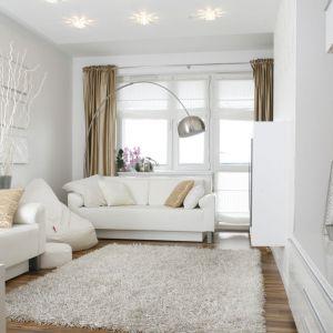 Jasny salon urządzono w bieli, do które idealnie pasuje ładne, ciepłe wybarwienie drewna. Projekt: Małgorzata Mazur. Fot. Bartosz Jarosz