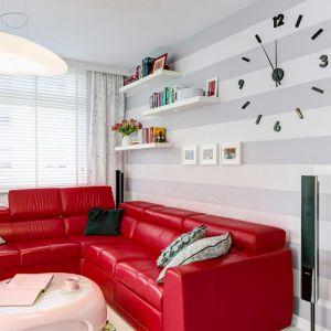 Czerwony narożnik stanowi efektowny akcent kolorystyczny w jasnym, nowoczesnym salonie. Projekt: Saje Architekci. Fot. foto&mohito