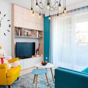 Żółty fotel-uszak w kolorowym, przytulnym salonie. Projekt: Krystyna Dziewanowska, pracownia Red Cube Design. Zdjęcia Mateusz Torbus 7TH IDEA